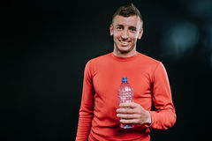 Attractive shot portrait of handsome smiling muscular Caucasian man wearing red sportswear with bottle of water, relaxing after in. Caucasian sportsman wearing Royalty Free Stock Image
