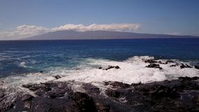 Attractive shot of water splashing against the cliffs on the background of big mountains mauna loa with the subaerial stock video footage