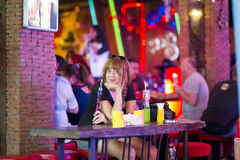 Attractive single woman smoking shisha and drinking at bar alone Stock Image