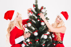 Attractive sisters in santa clothes and hats decorating Christmas tree Stock Images