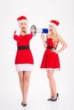 Attractive sisters twins in santa claus costumes speaking on loudspeaker Royalty Free Stock Image