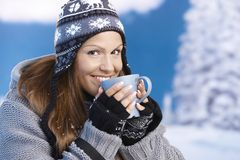 Attractive skier drinking hot drink smiling Stock Photos