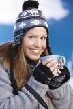 Attractive skier drinking hot drink smiling Stock Images