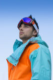 Attractive skier or snowboarder against blue sky Royalty Free Stock Image