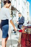 Attractive skillful businesswoman refilling the car. Women can do everything. Attractive serious skillful businesswoman standing near the car and looking at the Stock Photography