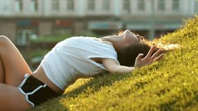 Attractive skinny young woman lying on the grass and hugging herself with her hands - then stand up stock footage