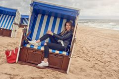 Attractive slender blond woman sitting in a beach hut royalty free stock photo