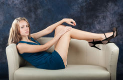 Attractive slender girl lies on divan Stock Images