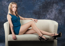 Attractive slender girl sitting on divan Stock Photography
