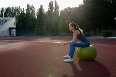 Attractive slender girl sitting on the fit ball at the stadium. Space for text royalty free stock photography