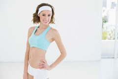 Attractive slender woman wearing sportswear posing in sports hall Stock Images