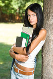 Attractive slender young student girl in the park. Royalty Free Stock Photos