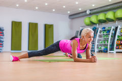 Attractive slim blonde middle-aged woman doing planking or stretching exercise on mat against colorful sport equipment stock images