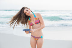 Attractive slim brown haired model in coloured bikini holding a tablet pc Royalty Free Stock Photo