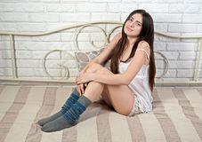 Attractive slim brunette in half-hose on bed Stock Images