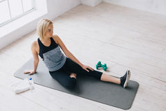 Attractive slim female doing stretching exercises on black mat in modern bright fitness center. Stock Images