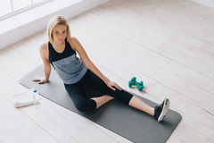 Attractive slim female doing stretching exercises on black mat in modern bright fitness center. Royalty Free Stock Photography