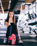 Attractive slim girl doing stretching exercises on black mat in modern fitness gym. Tired girl is relaxing after intensive workout Royalty Free Stock Photo