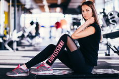 Attractive slim girl doing stretching exercises on black mat in modern fitness gym. Tired girl is relaxing after intensive workout Stock Photography