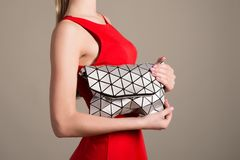Attractive slim girl in a red evening dress holds a stylish bag of silvery triangles Royalty Free Stock Photo