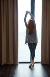 Attractive slim lady standing and stretching at the big window Stock Photo