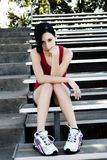 Hispanic Teen Girl Sitting On Metal Bleachers Red Top Shorts. Attractive Slim Latina Teen Girl Sitting Blue Shorts Red Top Metal Bleachers Outdoors Head Leaning stock image