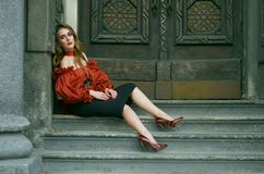 Attractive slim woman in a red elegant blouse and black skirt posing sitting on the stairs. Fashion photo stock image