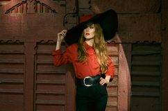 Attractive slim woman in a wide-brimmed hat, a red blouse and black pants posing against a vintage red door. Fashionable photo. stock photo