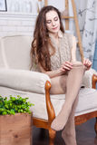 Attractive slim young brunette is wearing stockings. She sits in a big comfortable chair. Stock Photography