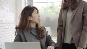 Attractive smart Asian business woman in smart casual wear working on laptop while sitting on desk while her angry manager. stock video footage