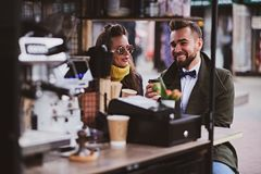 Attractive smart couple is enjoying coffee while sitting outside at small coffeesho stock images