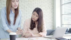Attractive smart creative Asian business women in smart casual wear working on laptop while sitting on desk on office desk. Women work at office concept stock footage