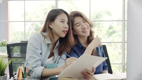 Attractive smart creative Asian business women in smart casual wear working on desktop while sitting on desk in office. stock footage