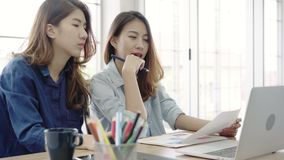Attractive smart creative Asian business women in smart casual wear working on laptop while sitting on desk in office. Women work at office concept stock video footage