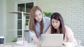 Attractive smart creative Asian business women in smart casual wear working on laptop while sitting on desk on office desk. Women work at office concept stock video