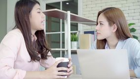 Attractive smart creative Asian business women in smart casual wear working on laptop while sitting on desk on office desk. Women work at office concept stock video footage