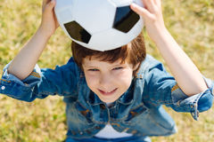 Attractive smart kid holding the ball up. Got it. Motivated energetic admirable child having fun while sitting on the grass and taking a break from playing royalty free stock photo