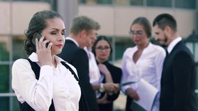 Attractive smart-looking business woman speaking on the phone and her colleagues standing in the background and chatting stock video