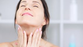 Attractive smiling adult woman applying anti-aging cream on neck and contour of chin close-up stock video