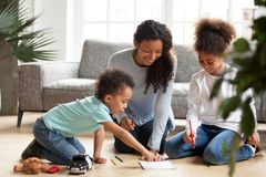 Happy African American mother drawing with children. Attractive smiling African American mother drawing with children sitting on warm floor in living room royalty free stock images