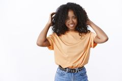 Attractive smiling african-american young woman touching curly strands check haircut smiling broadly apply haircare royalty free stock photos