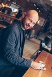 Attractive smiling bald man with coffee looking at camera in cafe royalty free stock photo