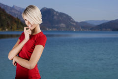 Woman by the lake. Attractive smiling blond woman in red dress standing beside lake looking puzzled Stock Image