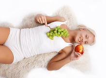 Attractive smiling blonde holding fruits Royalty Free Stock Photography