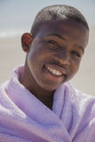 Attractive smiling boy at the beach. With a towel wrapped around him Stock Photo