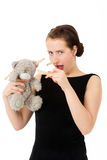 Attractive smiling brunette holding teddy bear grimacing with pe Stock Images