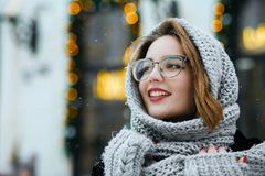 Attractive smiling woman wearing grey scarf and glasses posing at the street. Space for text. Attractive smiling brunette woman wearing grey scarf and glasses royalty free stock image
