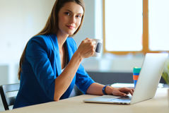 Attractive smiling business woman sitting at office desk, holding a cup of coffee. Stock Photo