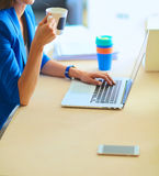 Attractive smiling business woman sitting at office desk, holding a cup of coffee. Stock Images