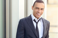Attractive smiling businessman with a loosened tie. And his collar unbuttoned looking at the camera, closeup head and shoulders Stock Photography